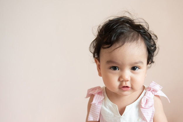 Portrait of a cute happy little asian baby girl she siting and look at camera isolated on background with copy space, baby expression concept