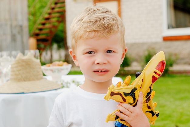 Portrait of cute happy little blond boy holding plane and car toys. adorable child walking in park on sunny day.