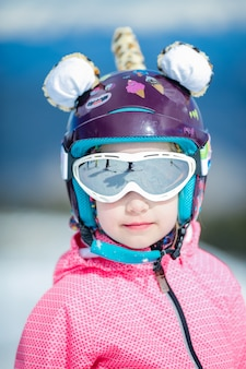 Portrait of cute happy skier girl in helmet and goggles in a winter ski resort