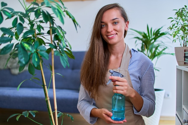 Portrait of cute happy young smiling attractive woman gardener in apron watering houseplants using spray bottle