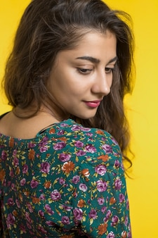 Portrait of a cute indian girl. young smiling woman on a yellow background.