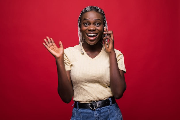 Portrait of cute joyful woman with trendy hairstyle talking on mobile phone and touching her brown locks isolated over red background