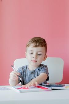 Portrait of cute kid boy at home making homework