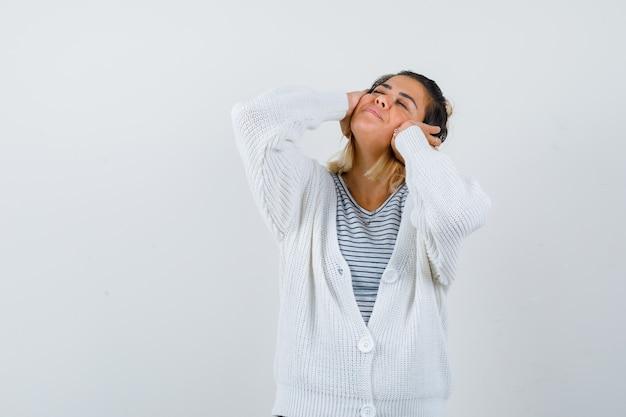 Ritratto di una signora carina che si tiene per mano sulle orecchie in maglietta, cardigan e sembra felice
