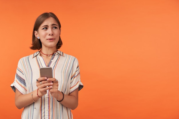 Portrait of cute lady holding a smartphone and watching to the right at copy space over orange wall showing her worries. wearing striped shirt, necklace and bracelets