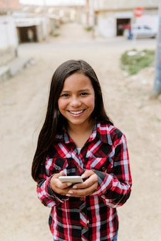 Portrait of cute latino girl using the mobile in shanty town. childhood concept.