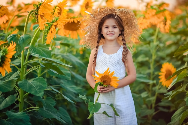 Portrait of a cute laughing girl in light clothes and a big straw hat at sunset on a field of sunflowers. she holds a big flower in her hands
