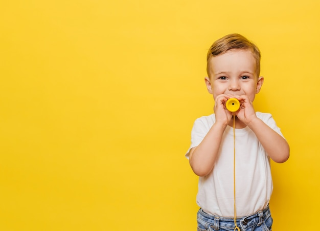 Portrait of a cute laughing little boy on a yellow background