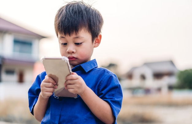 Portrait of cute little asian boy relaxing using digital smartphone.