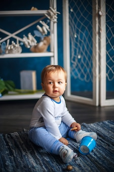 Portrait of a cute little baby boy in the interior with sea style