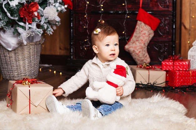 Portrait of cute little baby girl among christmas decorations