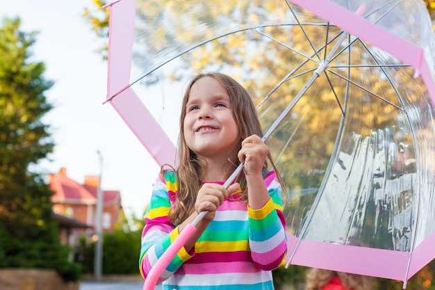 Portrait of a cute little baby girl walking near the house with an umbrella