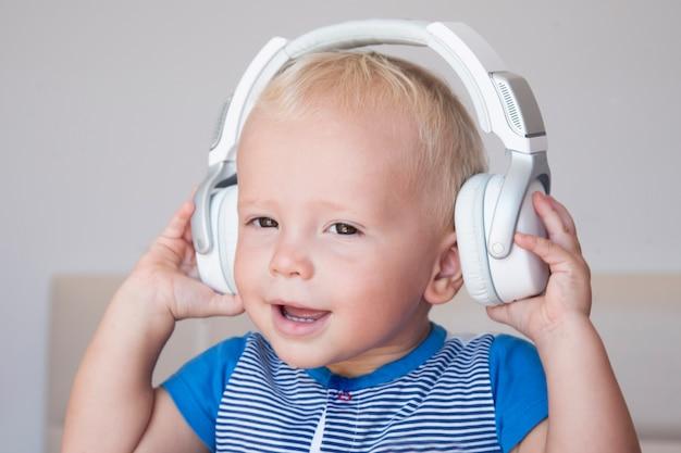 Portrait of a cute little blond boy listening to music