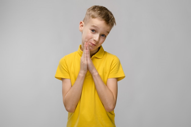 Portrait of cute little blonde caucasian boy in yellow t-shirt hoping asking for forgiveness on gray