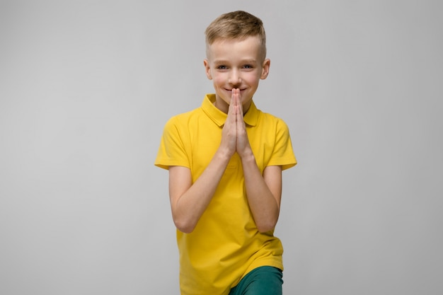 Portrait of cute little blonde caucasian boy in yellow t-shirt hoping on gray