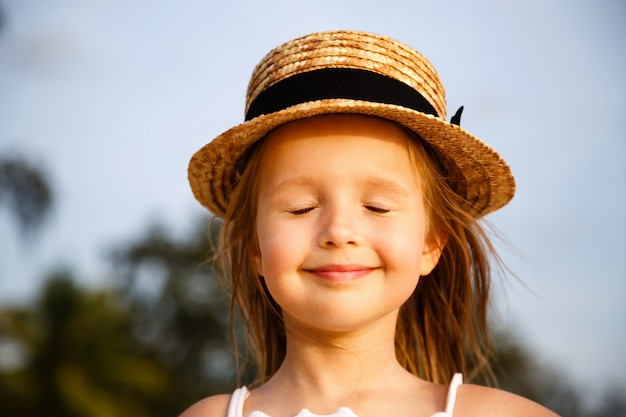 Portrait of cute little blonde girl in straw hat with closed eyes outdoor.