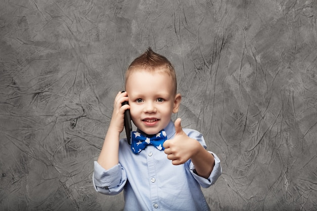 Portrait of a cute little boy in blue shirt and bow tie with mobile phone against gray textural