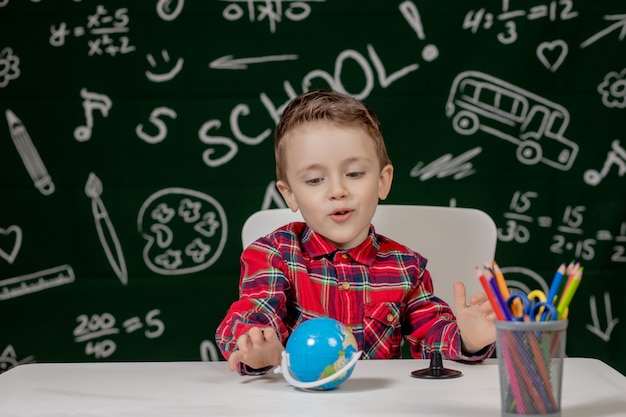 Portrait of cute little boy holding in hands small globe on blackboard background. ready for school. back to school.