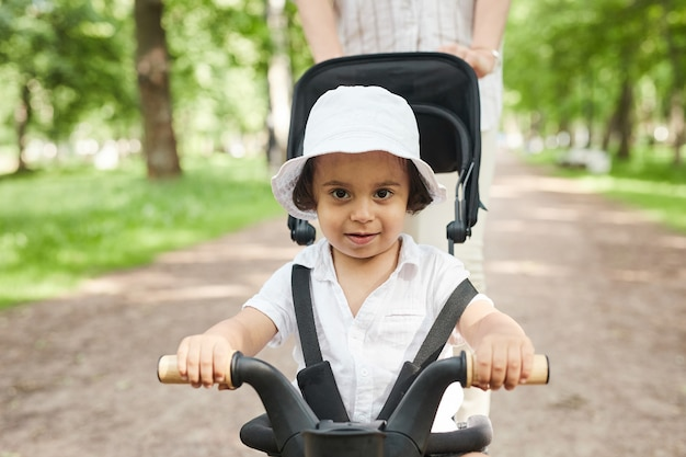 Portrait of cute little boy riding toddler bike and looking at camera during walk with mom in park