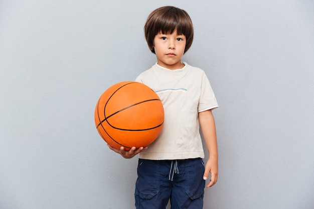 Portrait of cute little boy standing and holding basketball ball