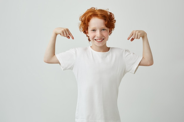 Portrait of cute little boy with ginger hair pointing with fingers of both hands on white t-shirt and smiling