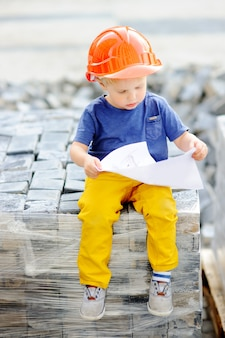 Portrait of cute little builder in hardhats reading construction drawing outdoors.