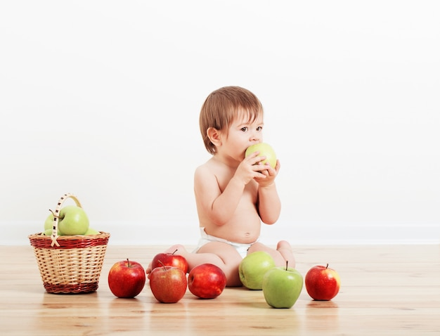 Portrait of a cute little child with apples indoor