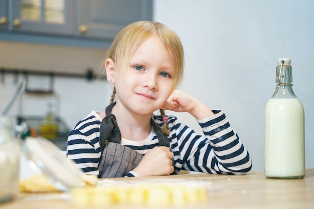 Portrait of a cute little girl in an apron preparing dough for cookies in the kitchen.