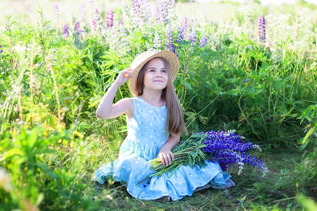 Portrait of cute little girl in hat in field of lupins. girl holding a bouquet of purple flowers in background of field of lupins.