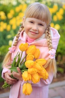 肖像画美しい花の背景に黄色いチューリップの花束を持っているかわいい女の子。ピンクのコートを着た女の子。
