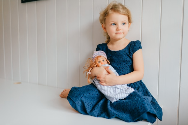 Portrait of cute little girl holds her lovely barbie, sits in bright baby room, looks aside