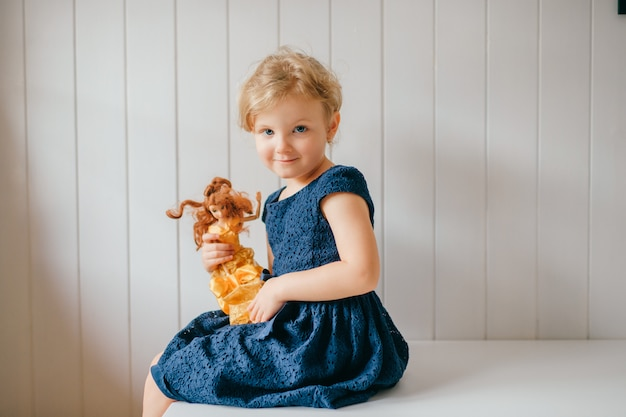 Portrait of cute little girl holds her lovely barbie, sits in bright baby room