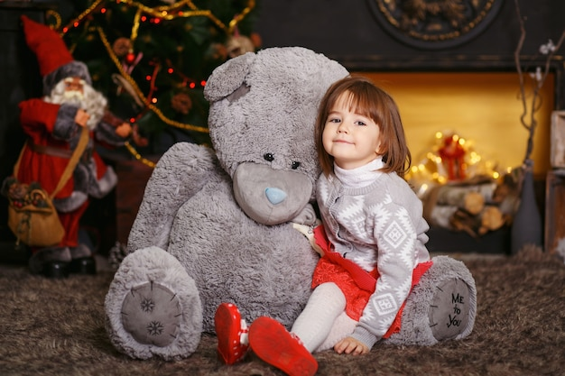 Portrait of a cute little girl hugging a soft gray teddy bear in interior with christmas decorations