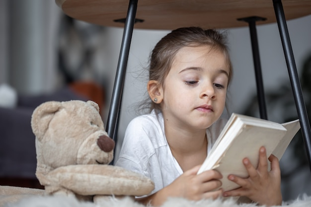 Portrait of a cute little girl reading a book at home, lying on the floor with her favorite toy.