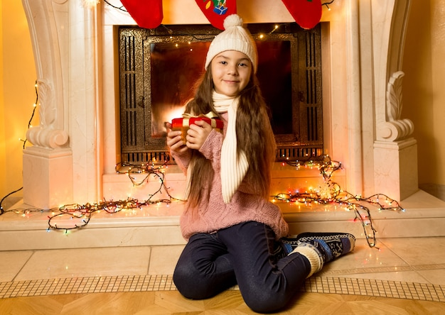 Portrait of cute little girl sitting at fireplace with christmas gift