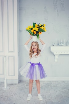 Portrait of cute little girl in skirt with yellow tulips flower