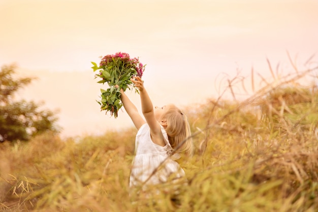 Portrait of cute little girl which holding hands bouquet of pink flowers on a field