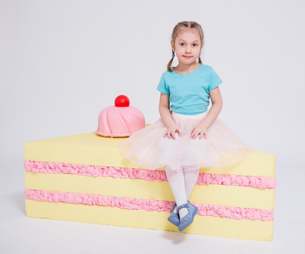 Portrait of cute little girl with big cake over white background