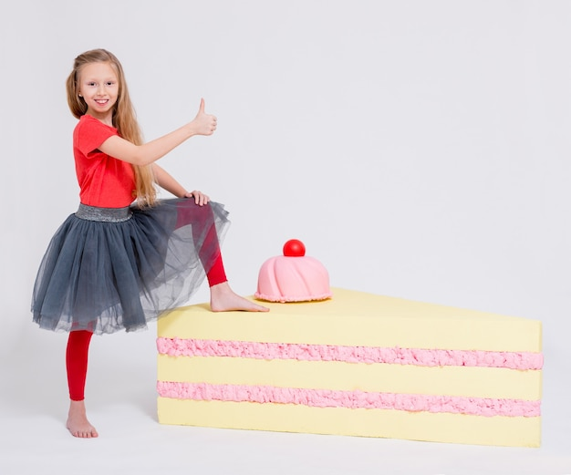 Portrait of cute little girl with big slice of cake thumbs up over white background