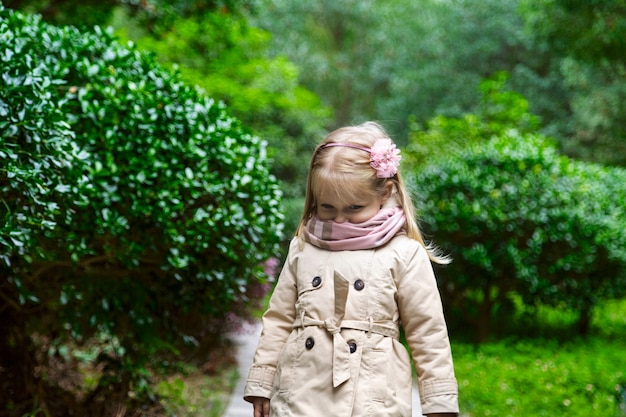Portrait of cute little girl with blonde hair in the park