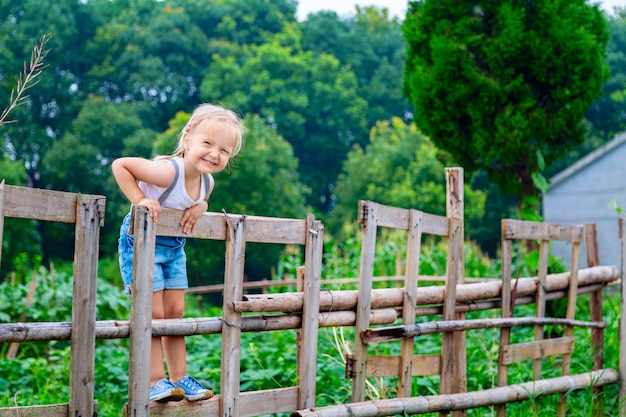 Portrait of cute little girl with blonde hair on a wooden fence