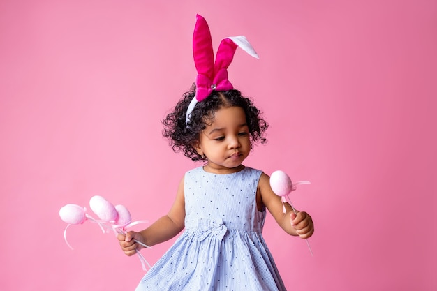 Portrait of a cute little girl with easter bunny ears on her head holding easter eggs. studio, pink background