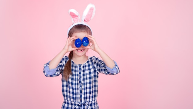Portrait of a cute little girl with easter eggs on a pink background.