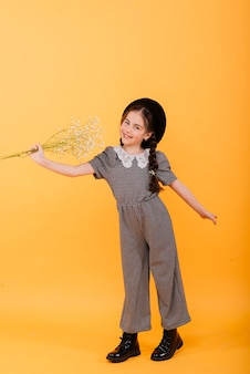Portrait of cute little girl with flower bouquet in the studio on yellow background.
