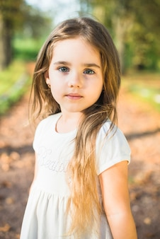 Portrait of a cute little girl with long hair standing in the park