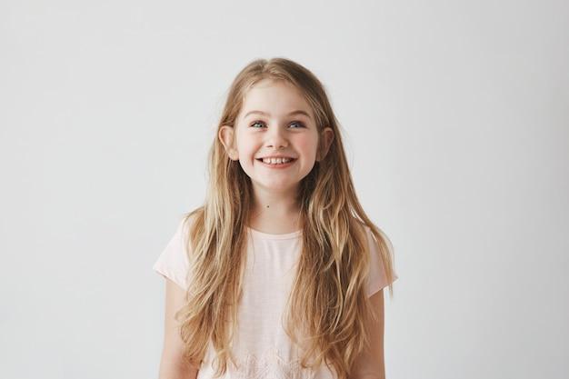 Ritratto della bambina sveglia con capelli chiari lunghi che sorride guardando al rialzo sui palloni volanti variopinti con l'espressione felice ed emozionante.
