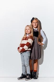 Il ritratto di bambine carine in vestiti di jeans alla moda che guarda l'obbiettivo in studio
