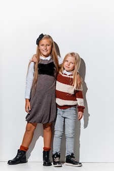 Il ritratto delle bambine sveglie nella posa alla moda dei vestiti dei jeans Foto Gratuite