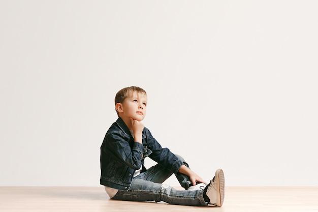 Ritratto del ragazzino sveglio in vestiti di jeans alla moda che guarda l'obbiettivo contro il muro bianco dello studio. concetto di moda per bambini