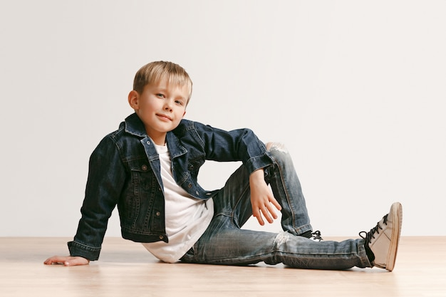 The portrait of cute little kid boy in stylish jeans clothes looking at camera against white studio wall.